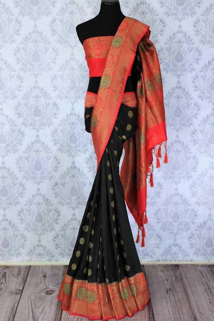 This black buta work muga banarsi silk sari complemented with a stunning red zari border and a heavily embroidered woven red pallu adds a touch of grace. Style it with a red designer blouse to strut at weddings or parties. Shop designer silk sarees, printed saris online or visit Pure Elegance store, USA. -full view