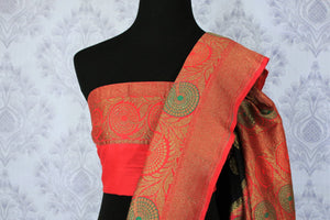 This black buta work muga banarsi silk sari complemented with a stunning red zari border and a heavily embroidered woven red pallu adds a touch of grace. Style it with a red designer blouse to strut at weddings or parties. Shop designer silk sarees, printed saris online or visit Pure Elegance store, USA. -blouse pallu