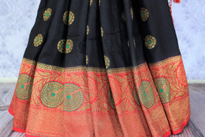 This black buta work muga banarsi silk sari complemented with a stunning red zari border and a heavily embroidered woven red pallu adds a touch of grace. Style it with a red designer blouse to strut at weddings or parties. Shop designer silk sarees, printed saris online or visit Pure Elegance store, USA. -pleats