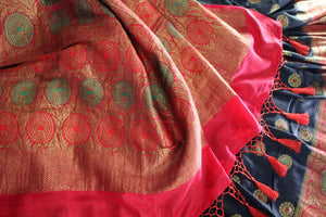 This black buta work muga banarsi silk sari complemented with a stunning red zari border and a heavily embroidered woven red pallu adds a touch of grace. Style it with a red designer blouse to strut at weddings or parties. Shop designer silk sarees, printed saris online or visit Pure Elegance store, USA. -details
