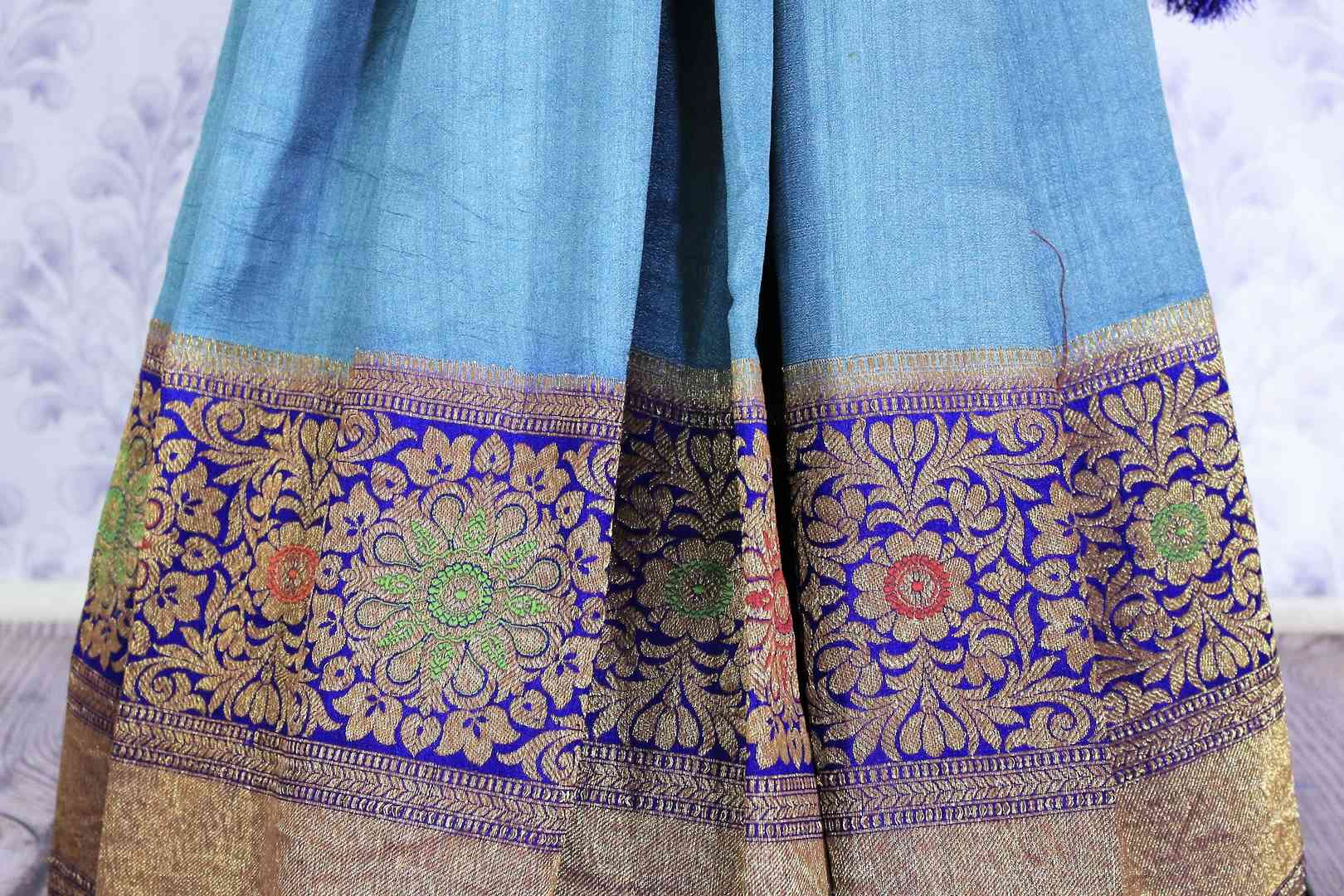 Dress up like a chic in this blue half-half designer muga banarsi silk saree. Complemented with a royal blue zari embroidered blouse and a heavily woven pallu, you will look no less than an Indian traditional lady. Shop designer sarees, printed saress, ikkat saris online or visit Pure Elegance store, USA.-pleats
