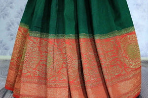 The ever-graceful green with red zari embroidered muga banarsi silk saree is a women's must-have. The traditional colors flowing together with the gorgeous blend of zari artwork. Take this stunner to parties, gala events and weddings. Shop this designer sari, printed sarees online or visit Pure Elegance store in USA.-pleats