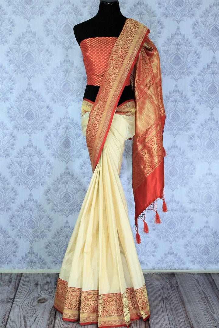 Embrace the divinity of a traditional Indian woman in this classic cream and red-hued muga banarsi silk saree. The contrasting red zari blouse accompanied with the rich red zari pallu looks spectacular. Shop designer silk saris, handloom sarees, ikkat saris online or visit Pure Elegance store in USA. -full view
