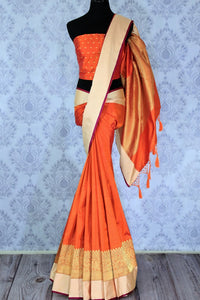 This plush yet royal orange traditional muga banarsi silk saree comes with a buta work orange designer blouse. The heavily woven pallu complemented with the zari detailing is crafted to perfection. Shop chanderi silk sarees, banarsi silk saris, ikkat sarees online or visit Pure Elegance store in USA. -full view
