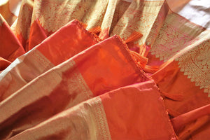 This plush yet royal orange traditional muga banarsi silk saree comes with a buta work orange designer blouse. The heavily woven pallu complemented with the zari detailing is crafted to perfection. Shop chanderi silk sarees, banarsi silk saris, ikkat sarees online or visit Pure Elegance store in USA. -details