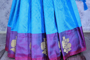 Dive into the elegance of this vibrant blue colored floral muga banarsi silk sari. It comes with a gorgeous designer purple woven border and pallu to create a pretty color block. It comes with a blue blouse. Shop banarsi silk sari, ikkat saris, printed sarees online or visit Pure Elegance store, USA. -pleats