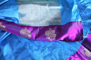 Dive into the elegance of this vibrant blue colored floral muga banarsi silk sari. It comes with a gorgeous designer purple woven border and pallu to create a pretty color block. It comes with a blue blouse. Shop banarsi silk sari, ikkat saris, printed sarees online or visit Pure Elegance store, USA. -details