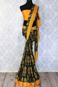 Look slender and suave in this designer black crepe silk printed sari with a stunning yellow border. Take this to work meetings and casual getaways.  Complete the look with a contrasting yellow blouse. Shop such beautiful Indian designer silk sarees, georgette saris online or visit Pure Elegance store in USA. -full view
