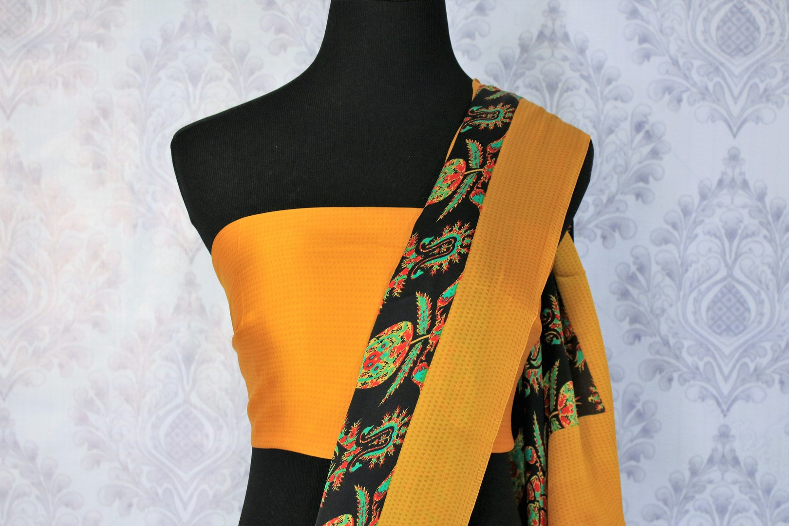 Look slender and suave in this designer black crepe silk printed sari with a stunning yellow border. Take this to work meetings and casual getaways.  Complete the look with a contrasting yellow blouse. Shop such beautiful Indian designer silk sarees, georgette saris online or visit Pure Elegance store in USA. -blouse pallu