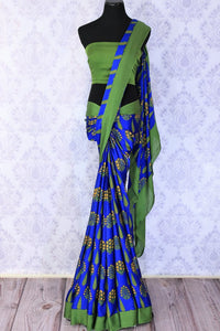 Strike a lasting impression in this handpainted blue floral crepe silk designer sari with stunning green border. The beautiful contrast with the green blouse looks dreamy. Shop unique and beautiful designer silk sarees, satin saris, kanjeevaram silk sarees online or visit Pure Elegance store in USA. -full view
