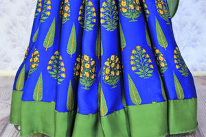 Strike a lasting impression in this handpainted blue floral crepe silk designer sari with stunning green border. The beautiful contrast with the green blouse looks dreamy. Shop unique and beautiful designer silk sarees, satin saris, kanjeevaram silk sarees online or visit Pure Elegance store in USA. -pleats