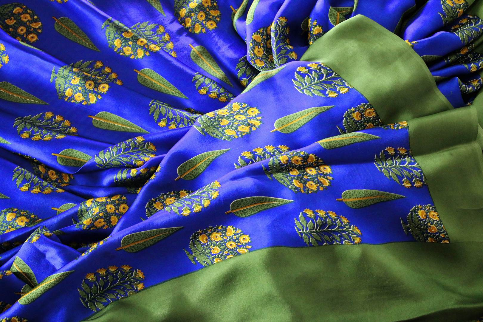 Strike a lasting impression in this handpainted blue floral crepe silk designer sari with stunning green border. The beautiful contrast with the green blouse looks dreamy. Shop unique and beautiful designer silk sarees, satin saris, kanjeevaram silk sarees online or visit Pure Elegance store in USA. -details