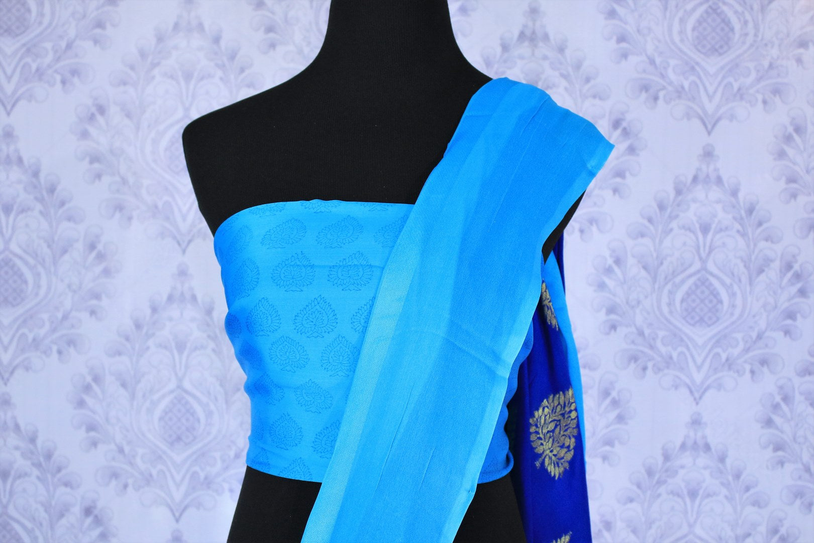 Feel the blues in this gorgeous half-half designer crepe silk blue colored sari. The stunning gold embroidered saree works well for both formal events and family gatherings. Style it with a light blue printed blouse to turn heads. Shop designer embroidered saris, silk saris online or visit Pure Elegance store in USA. -blouse pallu