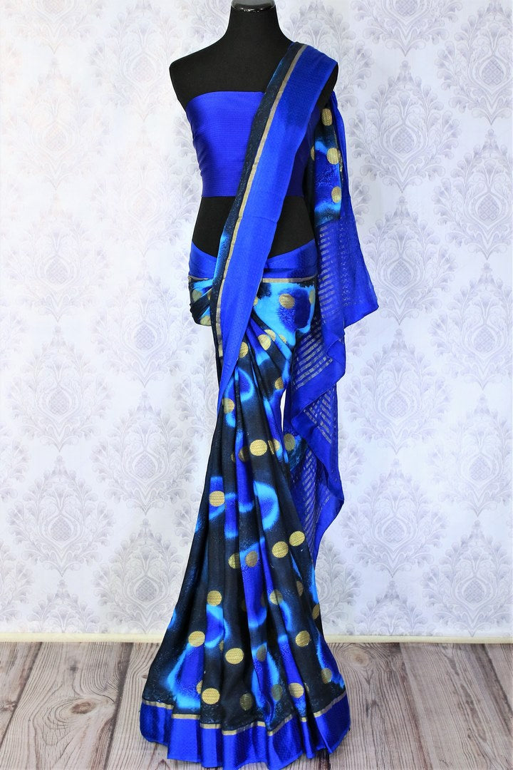 Feel the summer bliss in this easy breezy blue-hued printed crepe silk sari with a rich zari pallu. This handcrafted silk saree comes with a royal blue blouse and a glorious blue broad border flowing throughout. Shop such designer silk sarees, ikkat saris, handloom sarees online or visit Pure Elegance store in USA. -full view