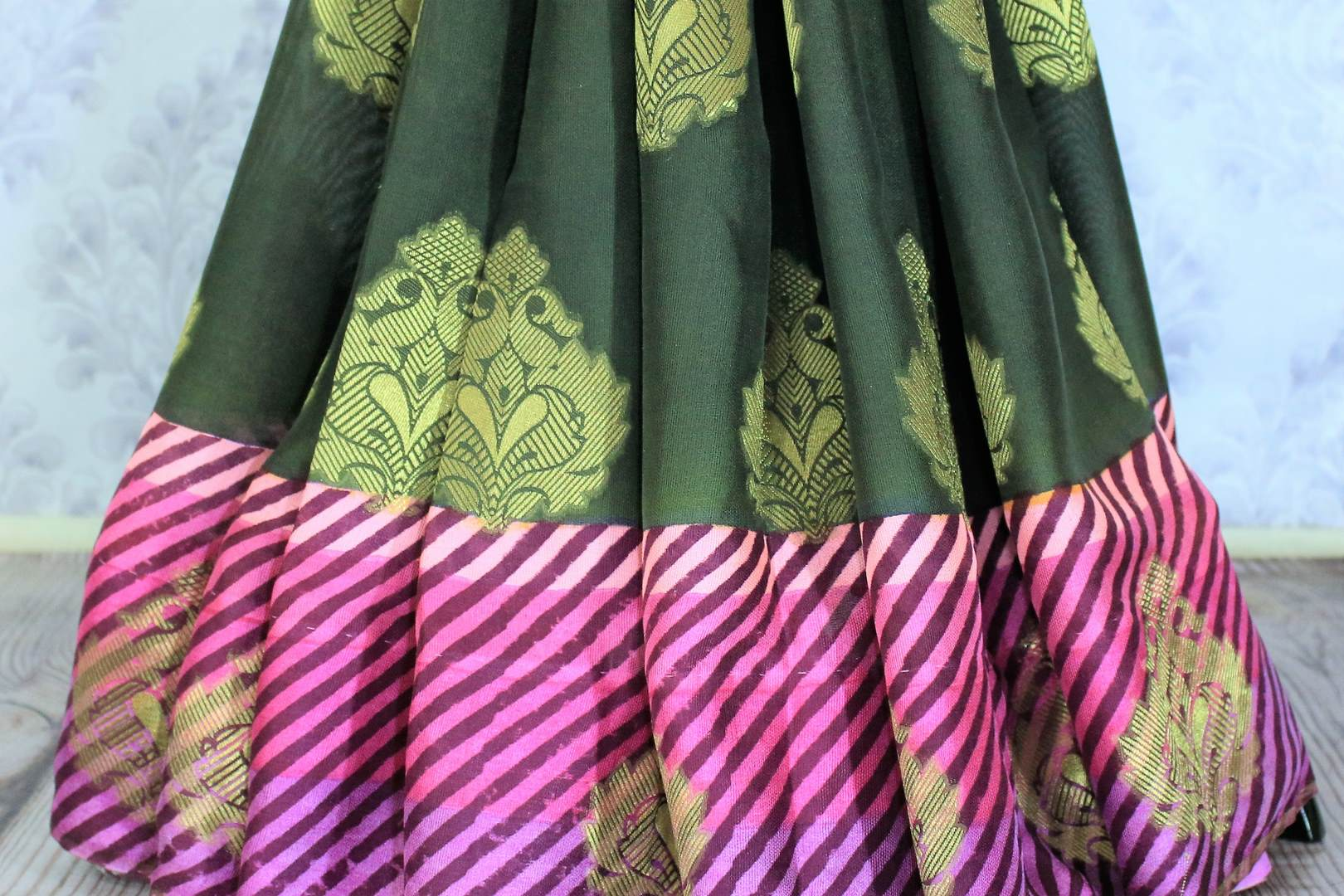 This solid green traditional saree with buta embroidery looks mesmerizing. The stunning pink leheriya border accompanied with a gorgeous green silk buta work embroidered blouse complemented with a heavy pallu looks heavenly. Shop the designer silk sarees, printed saris online or visit Pure Elegance store in USA. -pleats
