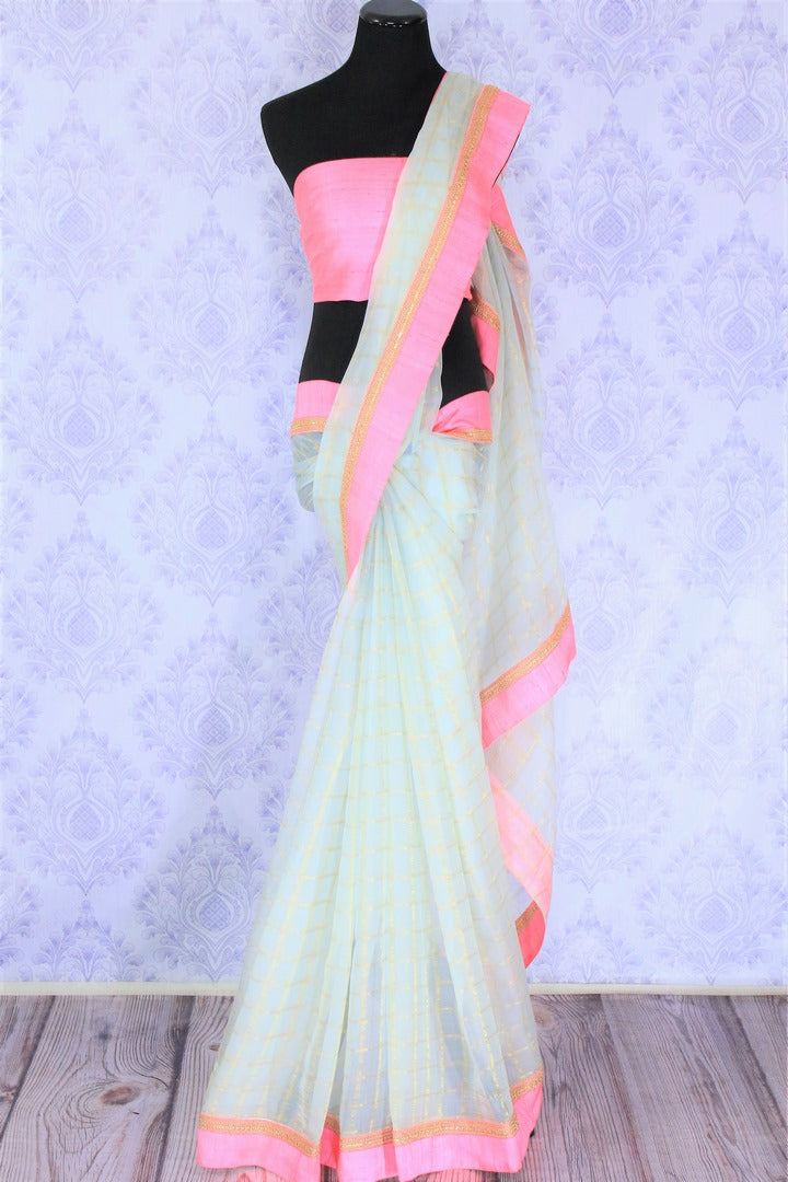 Grace in this summer staple blue organza saree with checkered pattern and a soft pink embroidered border flowing throughout. Style this suave sari with a blush pink blouse and slay effortlessly. Shop designer silk sari, chiffon saree, georgette saree online or visit Pure Elegance store, USA.-full view