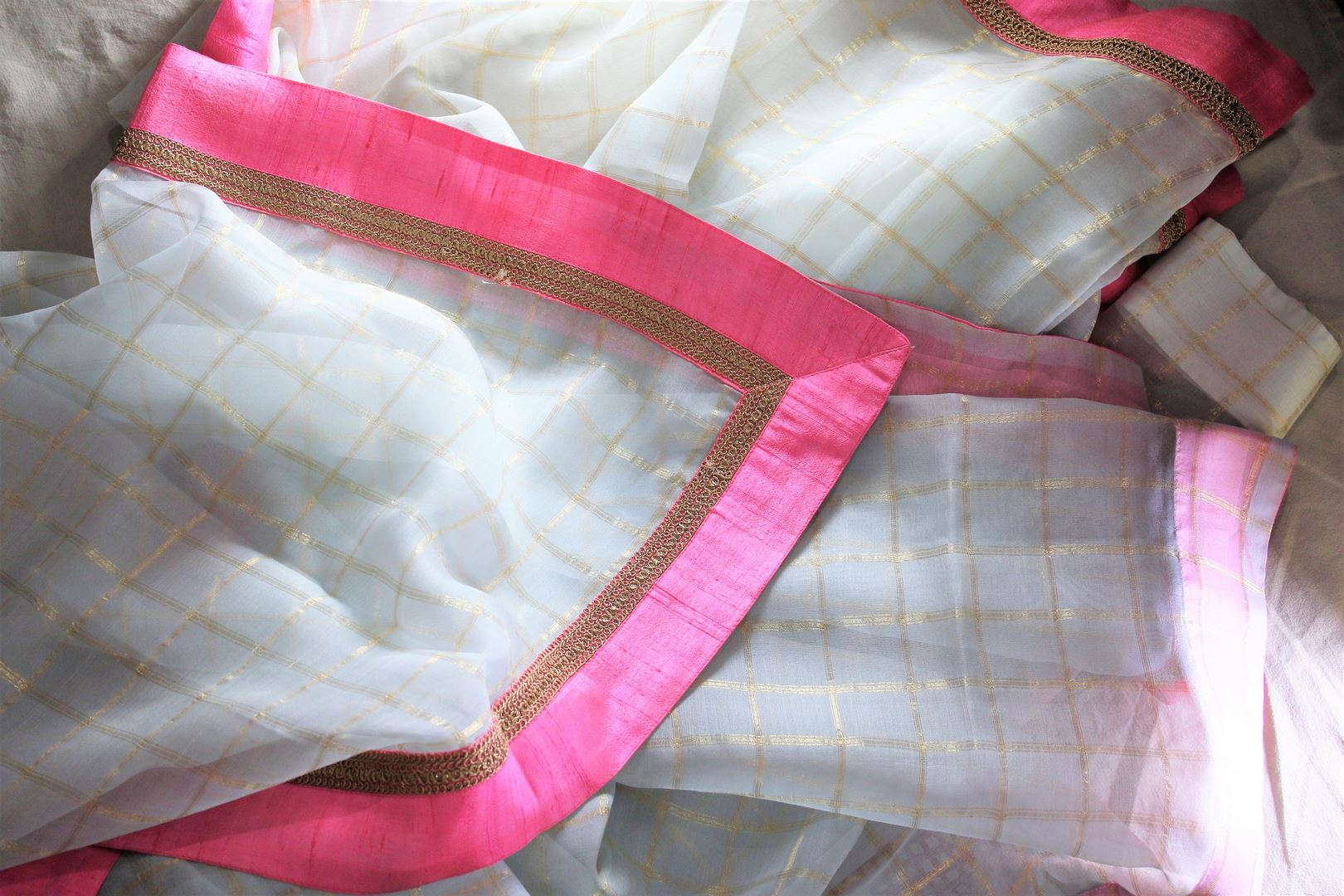 Grace in this summer staple blue organza saree with checkered pattern and a soft pink embroidered border flowing throughout. Style this suave sari with a blush pink blouse and slay effortlessly. Shop designer silk sari, chiffon saree, georgette saree online or visit Pure Elegance store, USA.-details