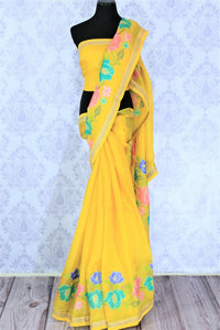 Gorge on this bright yellow floral work organza saree. It comes with a nuanced embroidered border and a bright yellow blouse with embroidered piping. The floral embroidery features vibrant colors to enhance the beauty. Shop such designer sarees, linen sari, georgette saree online or visit Pure Elegance store, USA. -full view