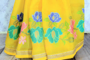 Gorge on this bright yellow floral work organza saree. It comes with a nuanced embroidered border and a bright yellow blouse with embroidered piping. The floral embroidery features vibrant colors to enhance the beauty. Shop such designer sarees, linen sari, georgette saree online or visit Pure Elegance store, USA. -pleats