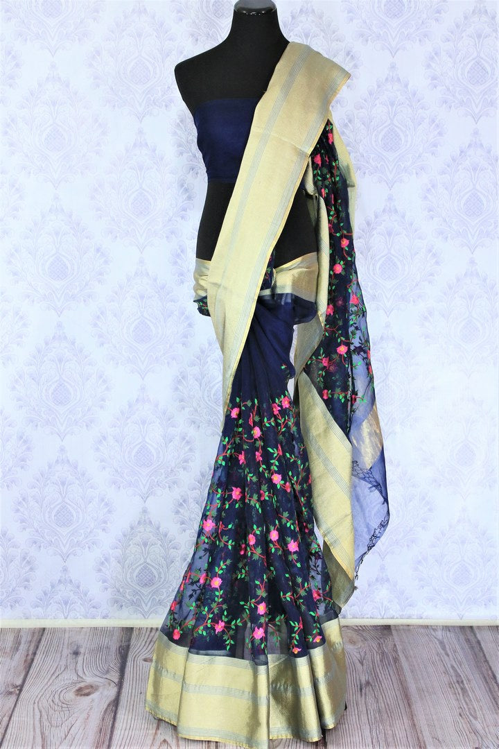 Emanate classic vibes in this gorgeous royal blue floral work organza saree. It features wide zari border with intricate design all over. Style it with a plain blue blouse and strut to parties and events. Shop designer linen sarees, ikkat sari online or visit Pure Elegance store, USA.-full view