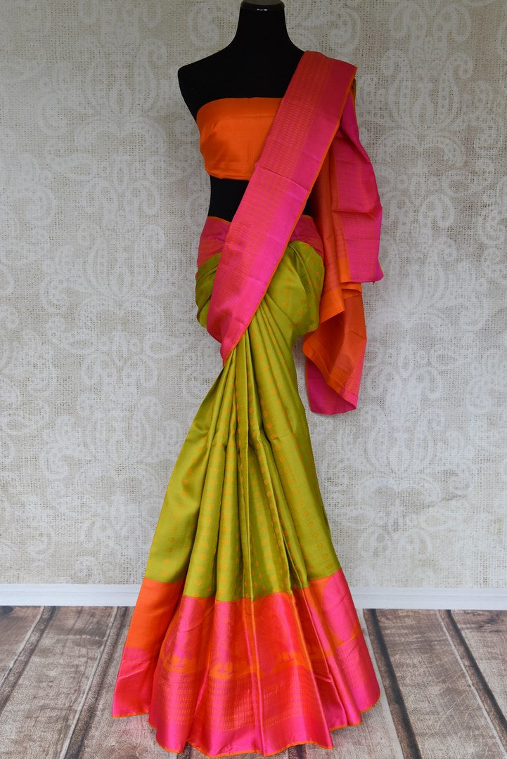 Be the dreamy damsel in this vibrant green and pink kanjivaram silk saree. The buta work all-over complemented with a pink contrast border and a hot orange blouse is a beautiful blend of colors. Shop banarsi silk saris, embroidered sarees, printed aris online or visit Pure Elegance store, USA. -full view