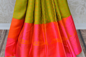 Be the dreamy damsel in this vibrant green and pink kanjivaram silk saree. The buta work all-over complemented with a pink contrast border and a hot orange blouse is a beautiful blend of colors. Shop banarsi silk saris, embroidered sarees, printed saris online or visit Pure Elegance store, USA. -pleats