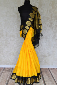 Put your gorgeous face forward in this uber-glamourous yellow kanjivaram silk saree with gold buta work detailing on the pallu. The rich black embroidered pallu complemented with black silk blouse is your wedding go-to. Shop handloom sarees, designer silk saris, chiffon sarees online or visit Pure Elegance store, USA. -full view