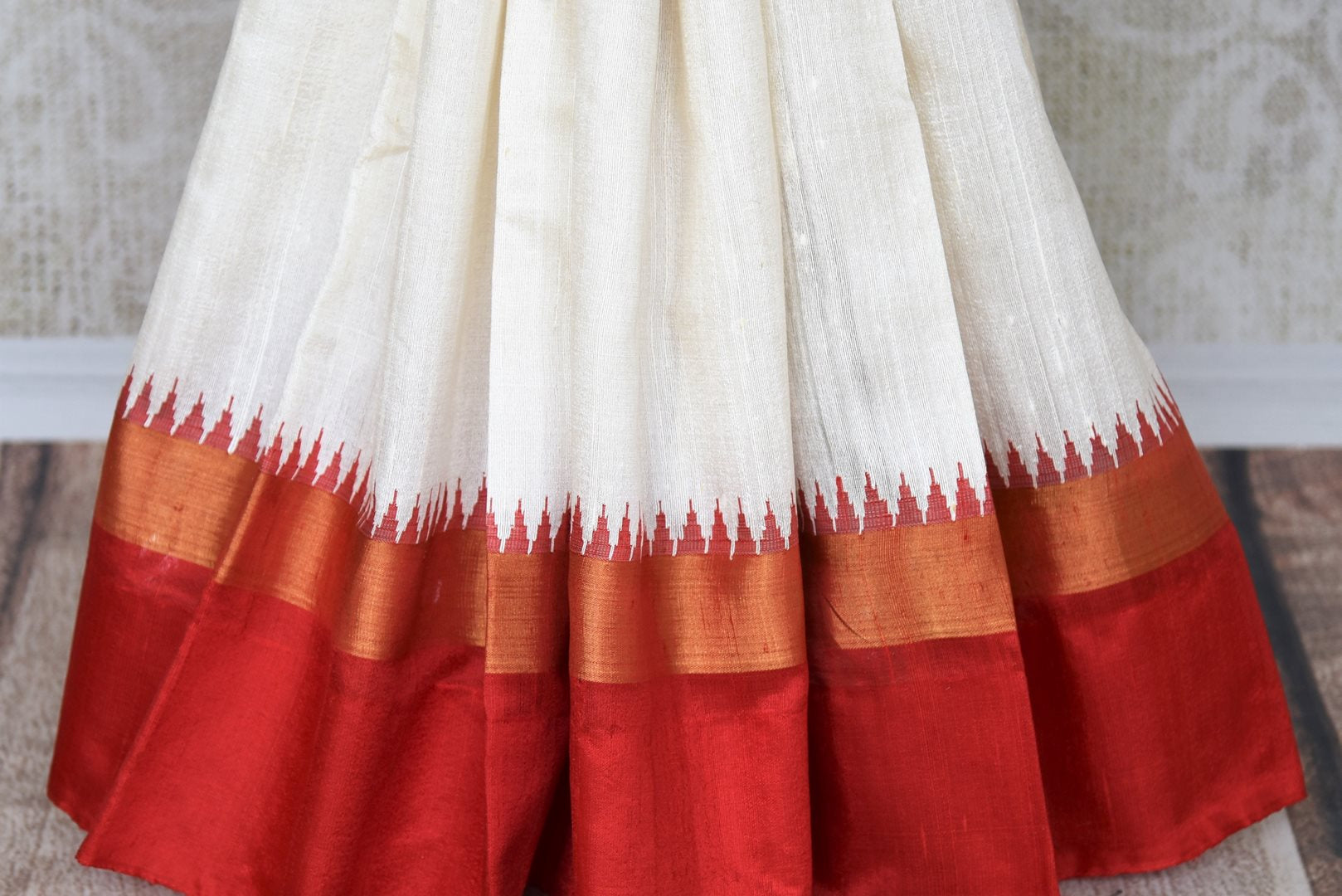 The classic white and red tussar silk designer sari is every woman's dream come true. Enhance your beauty in this silk saree with embroidered border and contrasting red blouse and strut to festivities. Shop designer silk sarees, kanjivaram silk saris, printed sarees online or visit Pure Elegance store, USA. -pleats