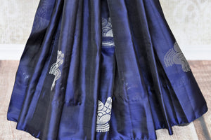 Elevate your authentic charm in this royal blue buta work kanjivaram silk saree. Graced with silver weave, this gorgeous sari comes with a heavily woven pallu and subtle blue blouse. Shop handcrafted silk sarees, printed sari, lehenga cholis, Indian dresses, ikkat sarees online or visit Pure Elegance store, USA.-pleats