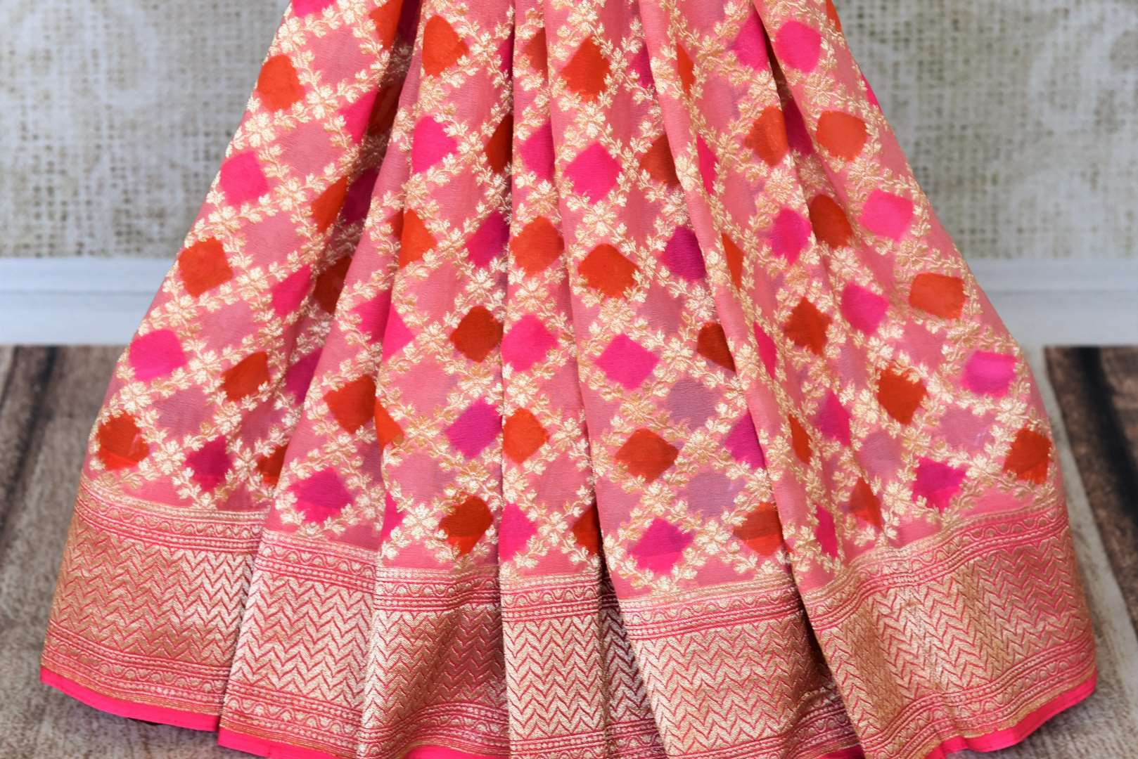 Exude feminity in this pink georgette banarsi silk saree. Perfect for summer-time weddings and parties, this sari comes with a stylish pink blouse. The sari has a zari border and handwoven motifs all over with a rich embroidered pallu. Shop such handcrafted silk sarees online or visit Pure Elegance store, USA. -pleats