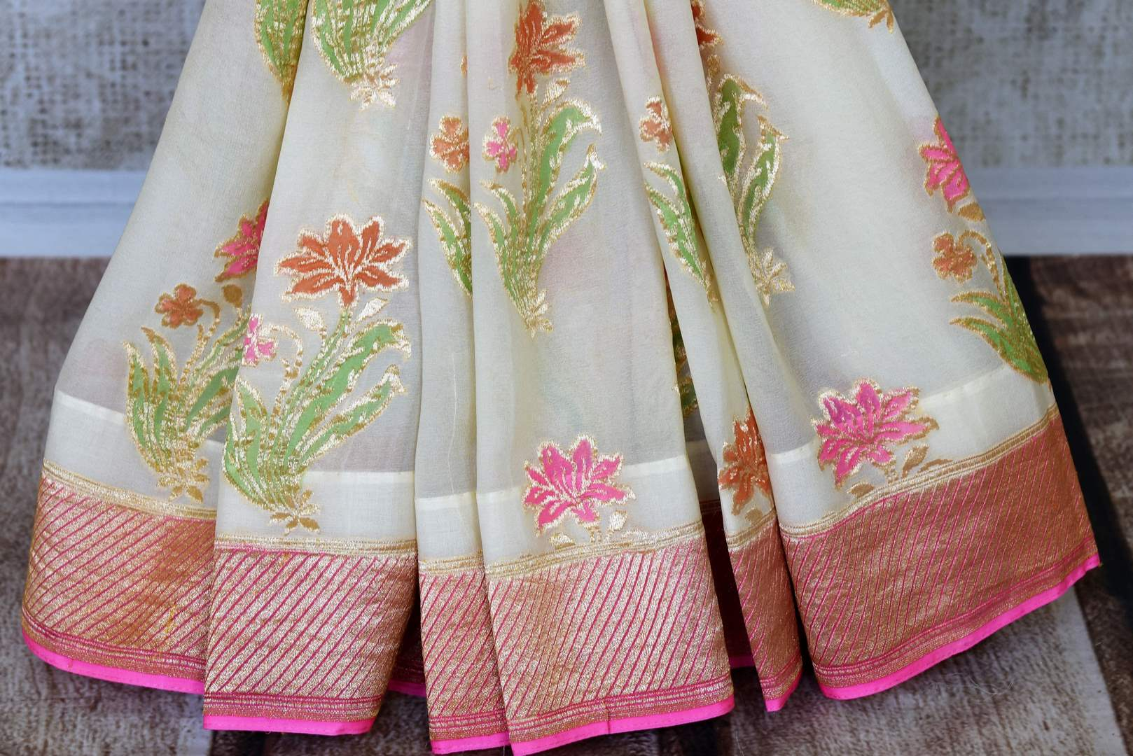 Strike a lasting impression in our white georgette banarasi silk saree. It has a gorgeous zari border accompanied with an equally stunning white zari blouse. Style it for social events, soirees and family gatherings. Shop such designer printed sari, embroidery saree online or visit Pure Elegance store, USA.-pleats