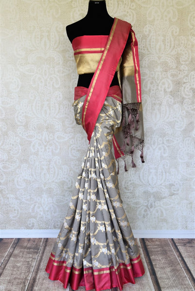 Personify finesse in this charming grey banarsi silk saree with a bright red border. The gorgeous sari features handwoven zari all over with visually appealing gold pallu to enhance its sheer beauty. It comes with a contrasting blouse. Shop designer saris, handloom sarees online or visit Pure Elegance store, USA. -full view
