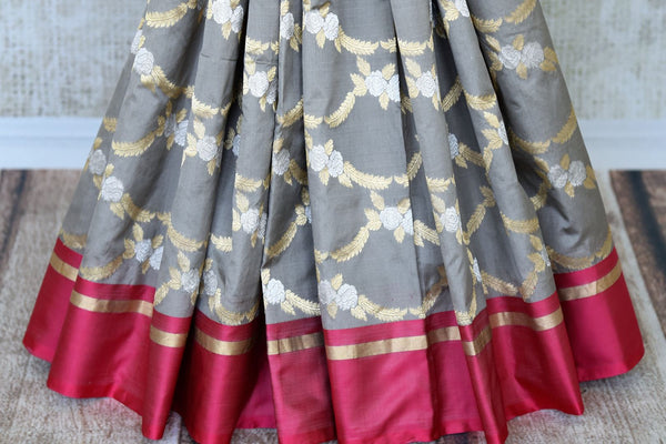 Personify finesse in this charming grey banarsi silk saree with a bright red border. The gorgeous sari features handwoven zari all over with visually appealing gold pallu to enhance its sheer beauty. It comes with a contrasting blouse. Shop designer saris, handloom sarees online or visit Pure Elegance store, USA. -pleats