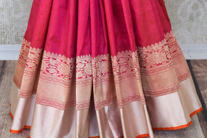 Channel traditional ladylike vibes in this pink banarsi silk saree with fine zari border. The signature bridal trousseau sari comes with a red and zari blouse with buta work. Shop such designer silk saris, banarsi silk saree, kanjeevaram silk sari online or visit Pure Elegance store, USA.-pleats