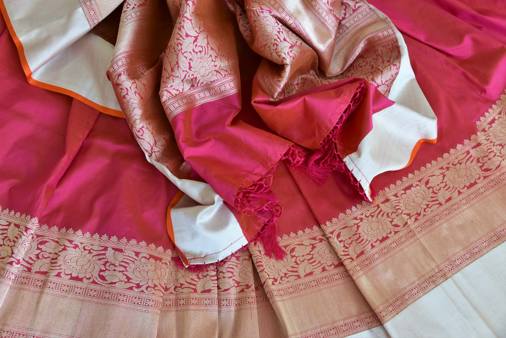 Channel traditional ladylike vibes in this pink banarsi silk saree with fine zari border. The signature bridal trousseau sari comes with a red and zari blouse with buta work. Shop such designer silk saris, banarsi silk saree, kanjeevaram silk sari online or visit Pure Elegance store, USA.-details