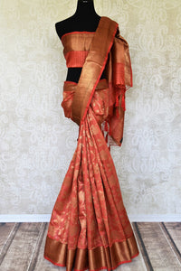 Adorn this flamboyant pink tussar banarsi silk saree with elongate zari detailing all over. It comes with a designer zari blouse and zari border to accentuate the finery of this ensemble. Shop designer silk sari, tussar sarees, handloom sari online or visit Pure Elegance store, USA.-full view