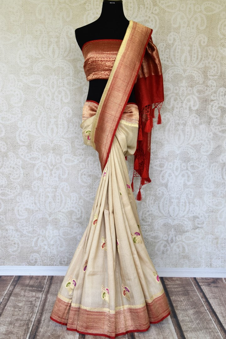 Treat yourself with this suave white khaddi banarsi silk saree paired with a stunning designer red blouse. Featuring zari work on the saree, and intricate buta work, it looks spectacular. Shop such designer silk sarees, printed sari, embroidery saree online or visit Pure Elegance store, USA.-full view