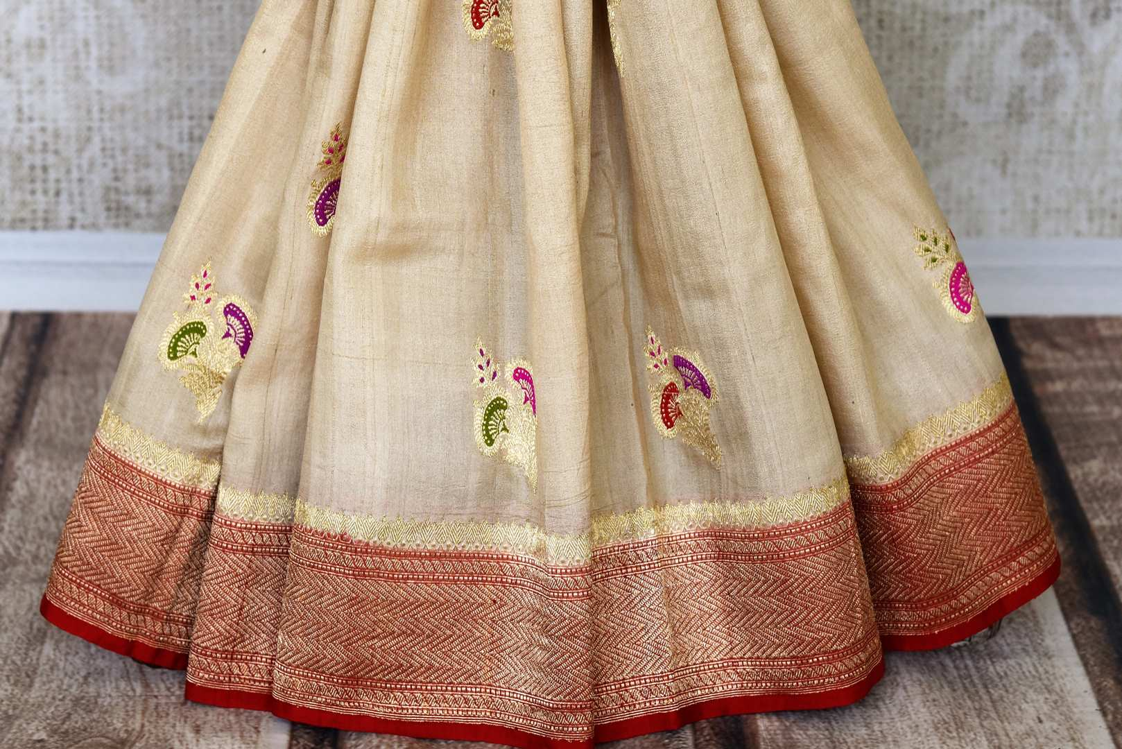 Treat yourself with this suave white khaddi banarsi silk saree paired with a stunning designer red blouse. Featuring zari work on the saree, and intricate buta work, it looks spectacular. Shop such designer silk sarees, printed sari, embroidery saree online or visit Pure Elegance store, USA.-pleats