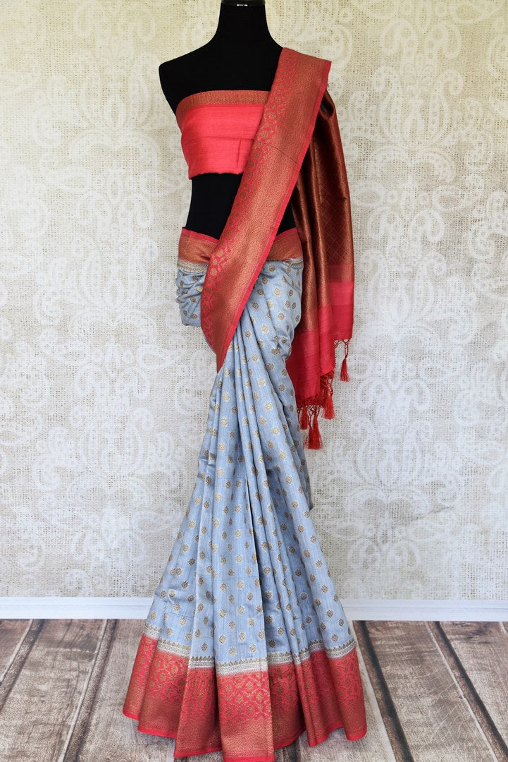 Satiate your dreamy appetite with this stunning grey tussar banarsi silk saree. It comes with a gold zari detailing on the deep red handwoven border. Style this saree with a pretty contrasting red blouse to make quite a statement. Shop designer embroidered sari online or visit Pure Elegance store, USA.-full view