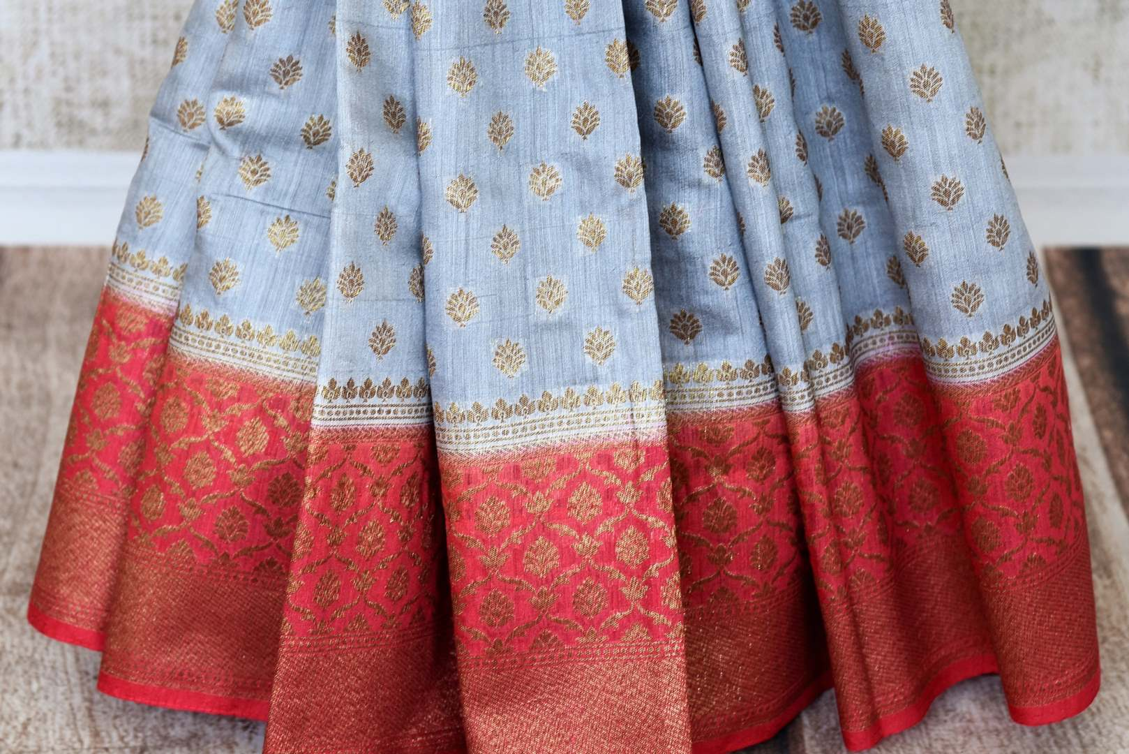 Satiate your dreamy appetite with this stunning grey tussar banarsi silk saree. It comes with a gold zari detailing on the deep red handwoven border. Style this saree with a pretty contrasting red blouse to make quite a statement. Shop designer embroidered sari online or visit Pure Elegance store, USA.-pleats