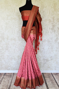 Paint a dreamy picture in this gorgeous pink tussar banarsi silk saree. It comes with heavily woven pallu and contrast red zari border to accentuate the elegance. You can style this beautiful sari with a contrasting red zari blouse. Shop such designer silk sari, printed saree online or visit Pure Elegance store, USA.-full view