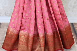 Paint a dreamy picture in this gorgeous pink tussar banarsi silk saree. It comes with heavily woven pallu and contrast red zari border to accentuate the elegance. You can style this beautiful sari with a contrasting red zari blouse. Shop such designer silk sari, printed saree online or visit Pure Elegance store, USA.-pleats