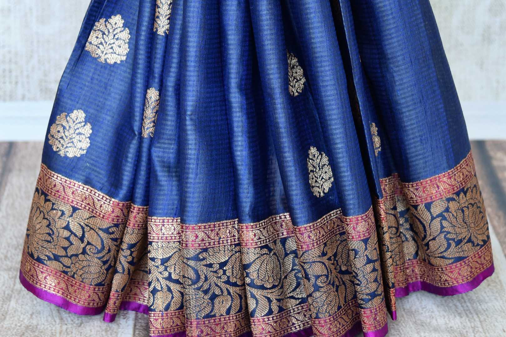 Swing in the gorgeous traditional royal blue tussar banarsi silk sari. It comes with a designer zari border and a contrasting pink designer blouse to steal the show. The buta work all over the sari exudes flamboyance of a kind. Shop designer silk sari, printed saree online or visit Pure Elegance store, USA.-pleats