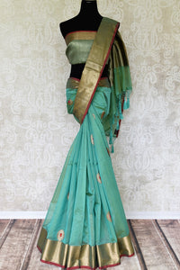 Your wedding quintessential is here, adorn the breath-taking sea green chanderi silk saree featuring buta work. The flamboyant sari showcases gold zari weave on its border and is styled with a stunning zari weave blouse to turn heads. Shop designer silk saris online or visit Pure Elegance store, USA.-full view