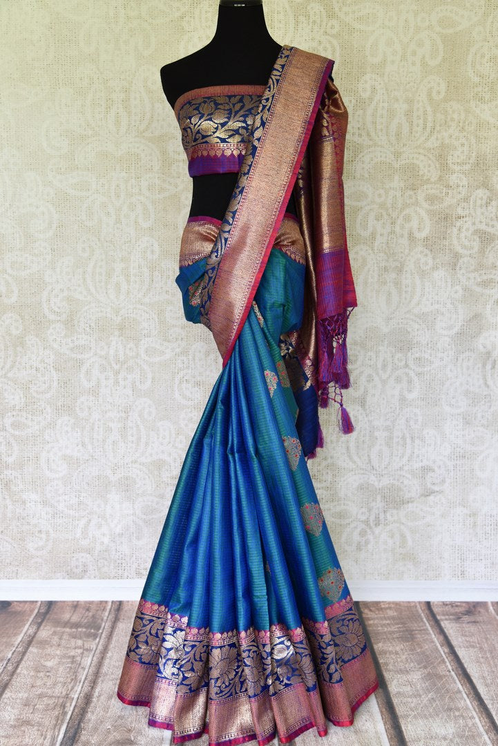 Indulge in the ethereal beauty of this royal blue tussar banarsi silk saree which comes with buta work and zari border. Style it with a designer blouse and steal the limelight as you sashay in a heavily embroidered pallu. Shop handloom sarees, georgette sari, ikkat saree online or visit Pure Elegance store, USA. -full view