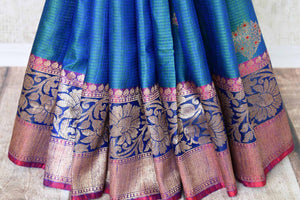 Indulge in the ethereal beauty of this royal blue tussar banarsi silk saree which comes with buta work and zari border. Style it with a designer blouse and steal the limelight as you sashay in a heavily embroidered pallu. Shop handloom sarees, georgette sari, ikkat saree online or visit Pure Elegance store, USA. -pleats