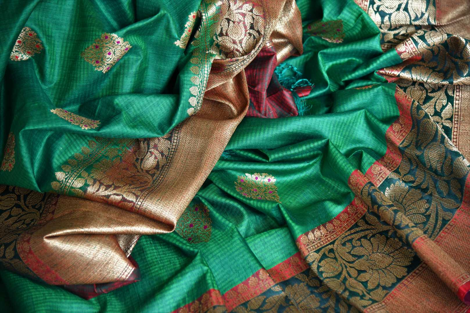 Flaunt your traditional side with our green tussar banarsi silk saree that features gorgeous buta work and intricately handwoven pallu. It blends perfectly with a muted woven designer blouse to ooze the elegance. Shop handloom sarees, linen sari, chiffon sari online or visit Pure Elegance store, USA.-details