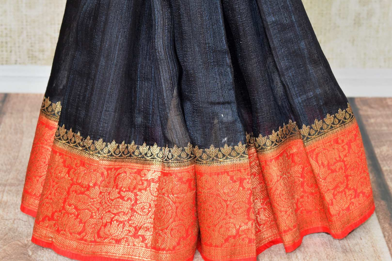 Enhance the subtle charm with classic black matka banarsi silk saree which comes with a vibrant red zari border. Strut to social events in this ensemble. Style it with a gorgeous red zari blouse to turn heads. Shop handloom sarees, kanjeevaram silk sari, linen sari online or visit Pure Elegance store, USA. -pleats
