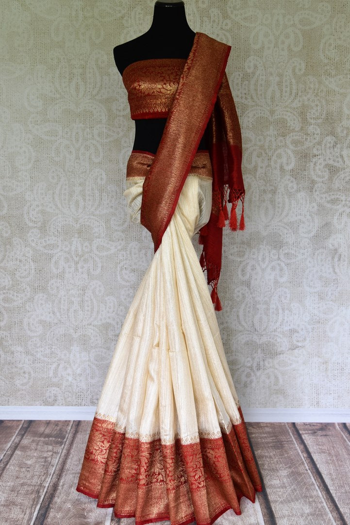 Fall in love with all things classic like this cream matka banarsi silk saree. The sensational combination of cream and red makes it even alluring. The red zari border and contrasting red blouse enhance the beauty. Shop designer silk saree, ikkat sari, georgette saree online or visit Pure Elegance store, USA.-full view