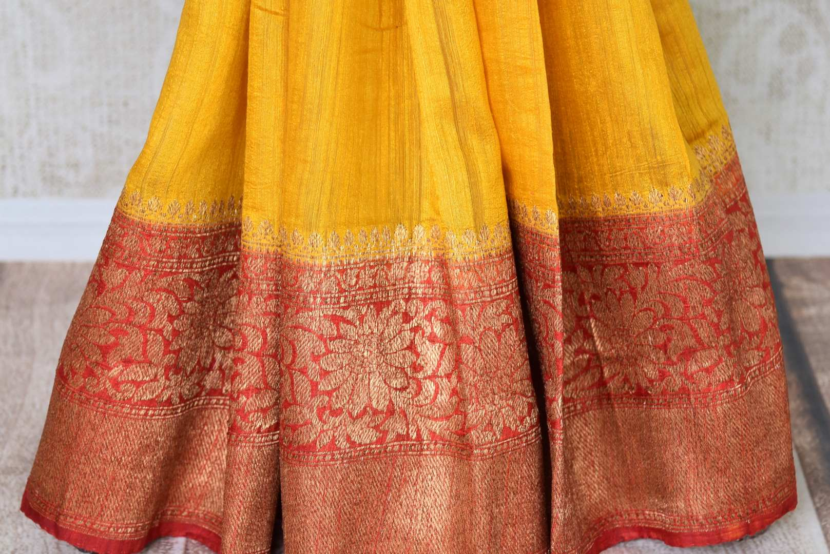 Exude a flair of elegance in this scintillating bright yellow matka banarsi silk saree. It comes with a gorgeous red zari border and complemented well with a contrasting red zari designer blouse. Shop handcrafted silk sarees, linen sari, georgette saree online or visit Pure Elegance store, USA.-pleats